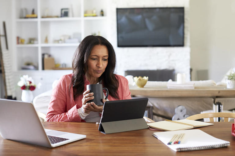 Middle aged woman sitting at a table reading using a tablet computer, holding a cup, front view